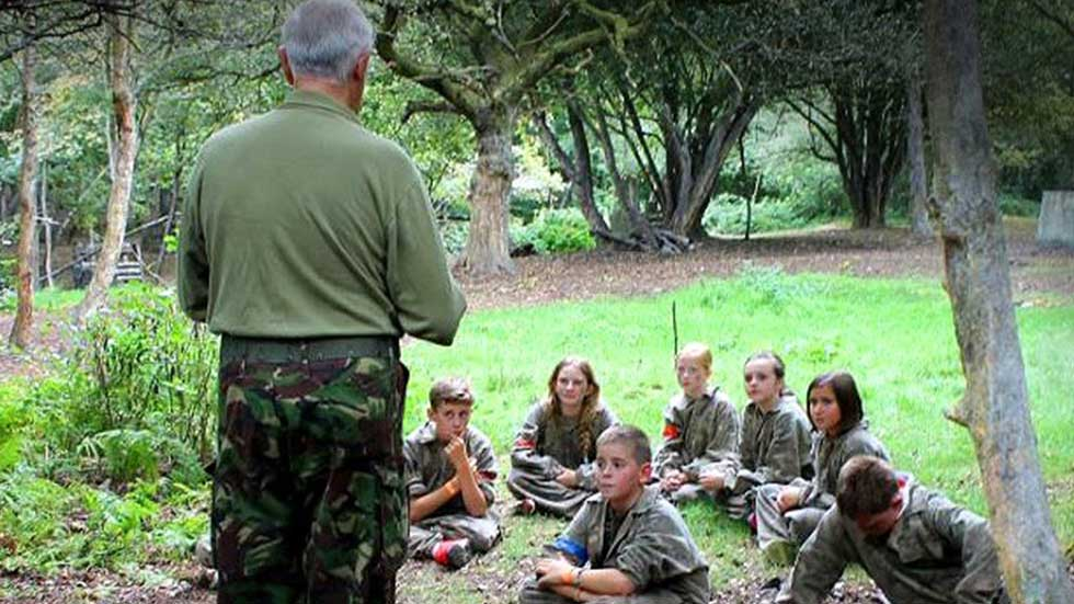 kids learn bushcraft survival skills from instructor