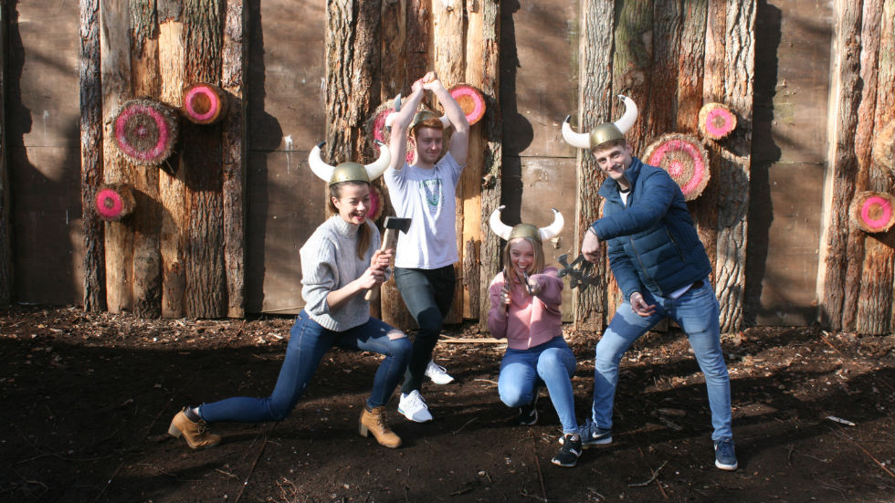 family group of all ages on axe throwing range