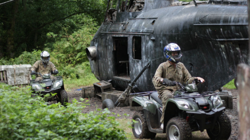quad trekking past downed military helicopter