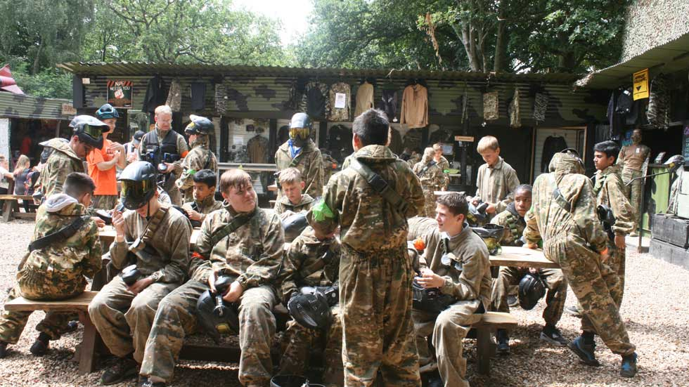 group of young players in paintball gear sitting at bench