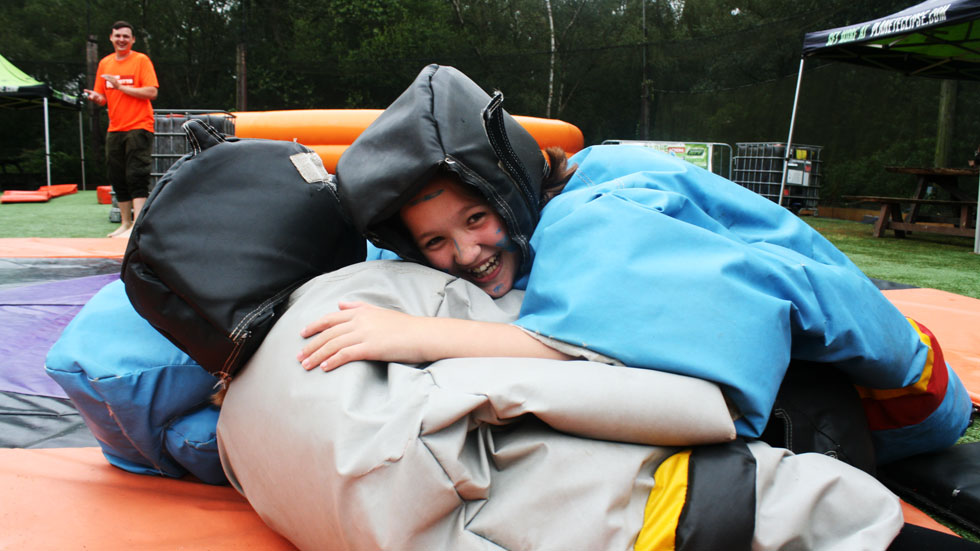 two juniors in inflatable sumo suits