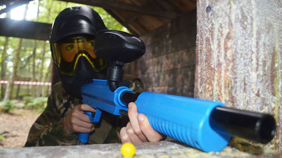 young player in paintball mask holds mini paintball gun