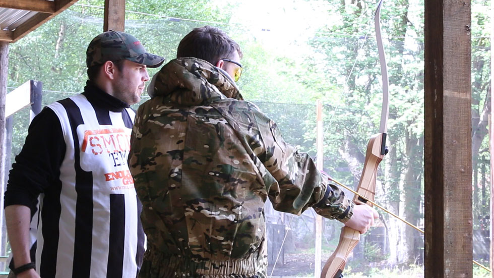 instructor helps archer improve shooting form