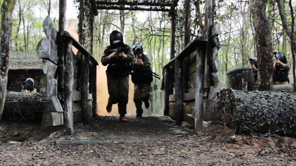 group of young players crossing the bridge in paintball game zone