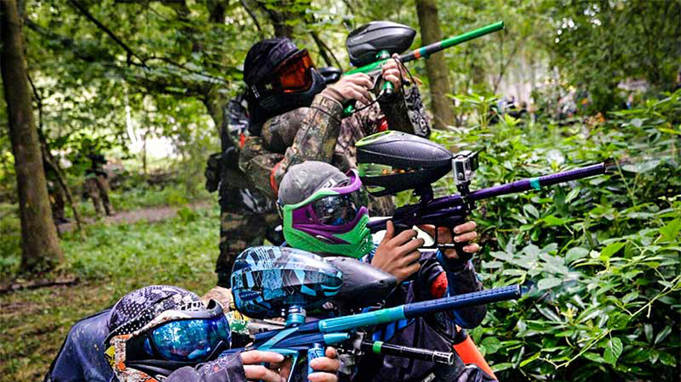 3 paintballers with brightly coloured markers and masks