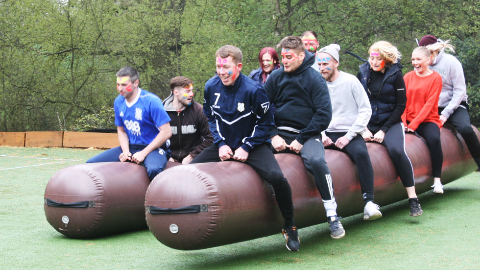 two groups team build using inflatable sausage racing