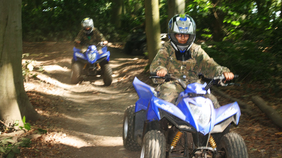 two younger quad bikers ride through a trail