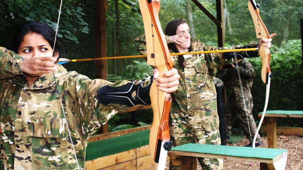 two girls shooting bows at the archery target range