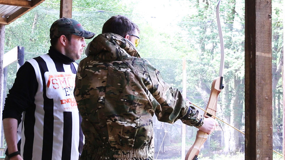 player with bow being supervised during shot