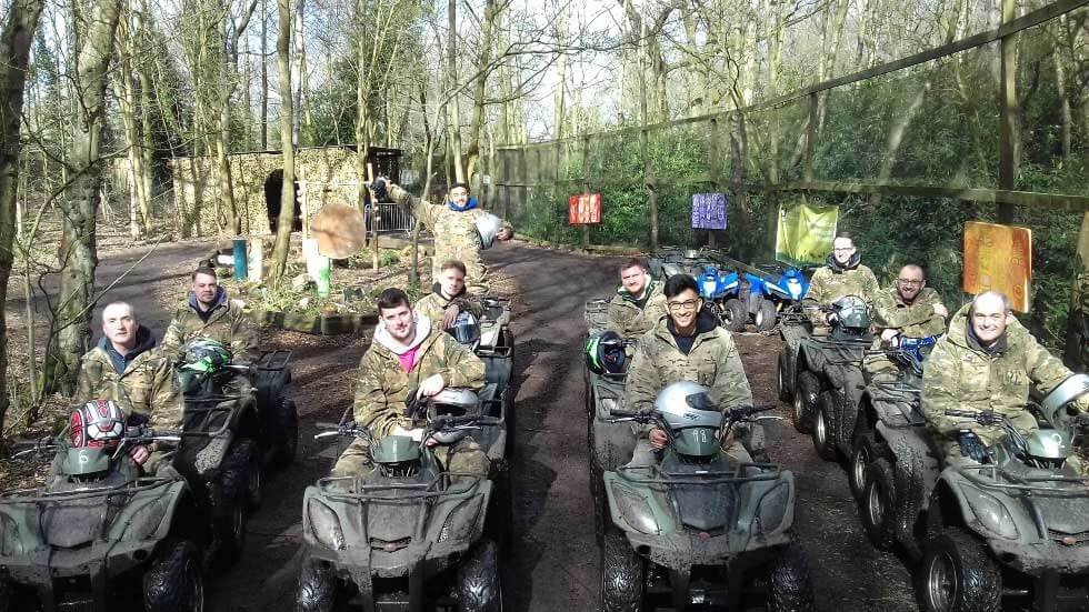 players ride through rhododendron woodland on quad bikes