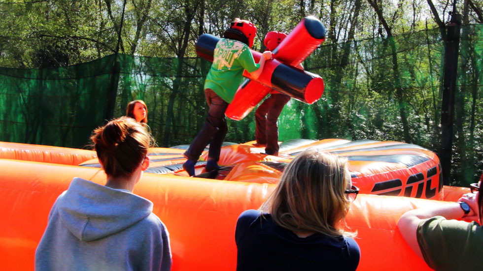 party of young players watch friends take part in inflatable combat