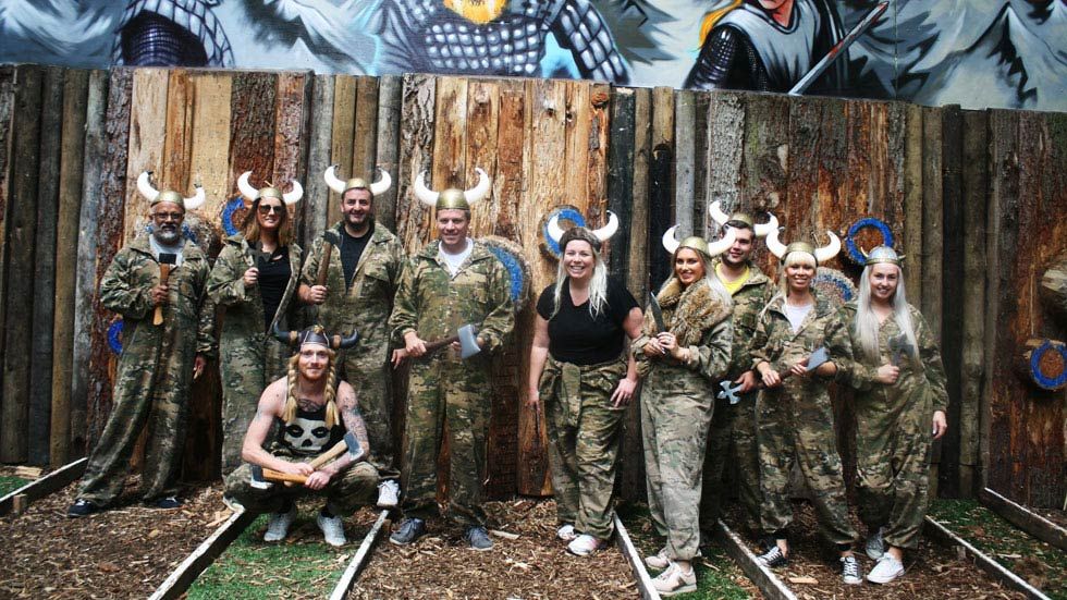 happy axe throwing group with viking hats