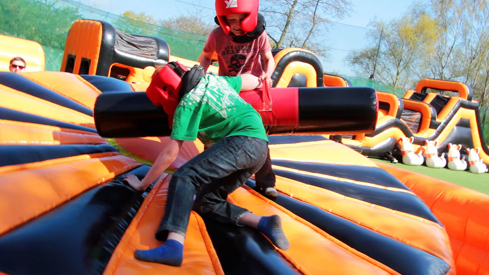two young players in protective gear fighting on inflatables