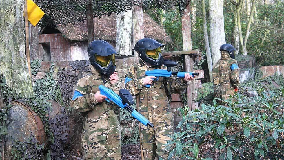three happy birthday party members in full paintball equipment