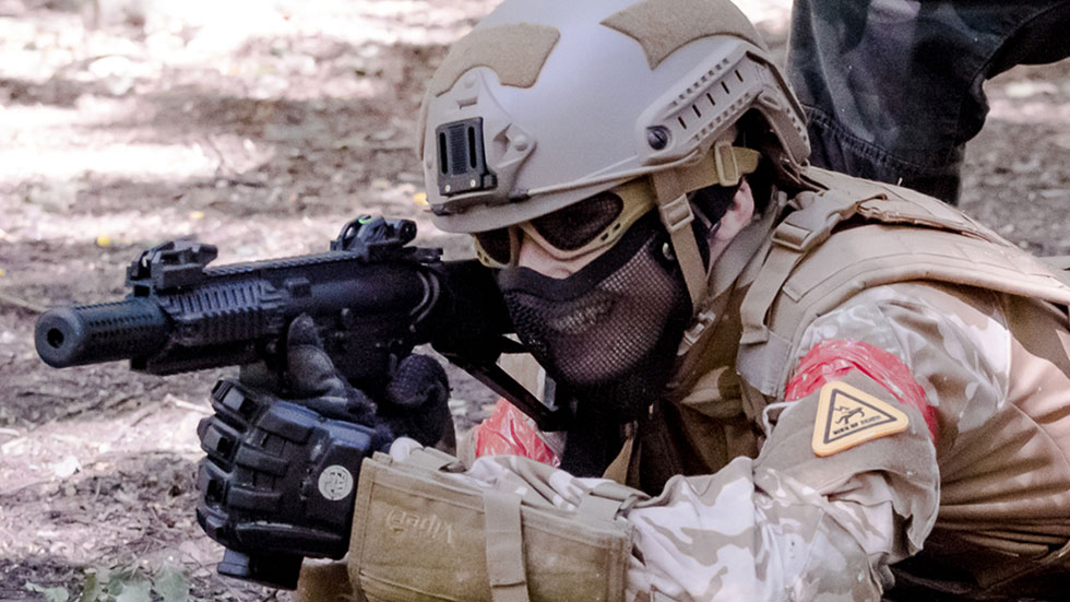 prone airsoft player in full kit fires at attackers