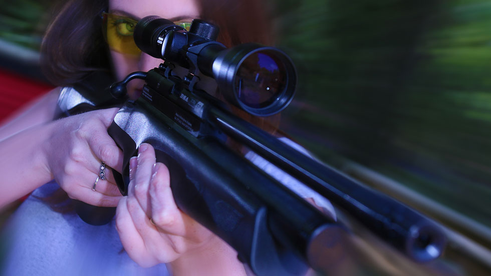 woman aiming air rifle during hen party