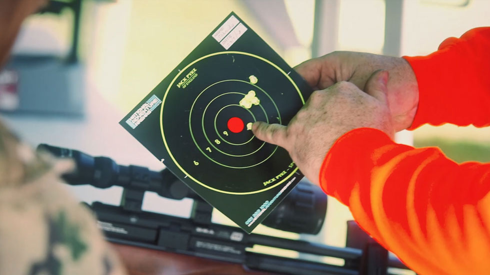 instructor holds target and points at near bullseye