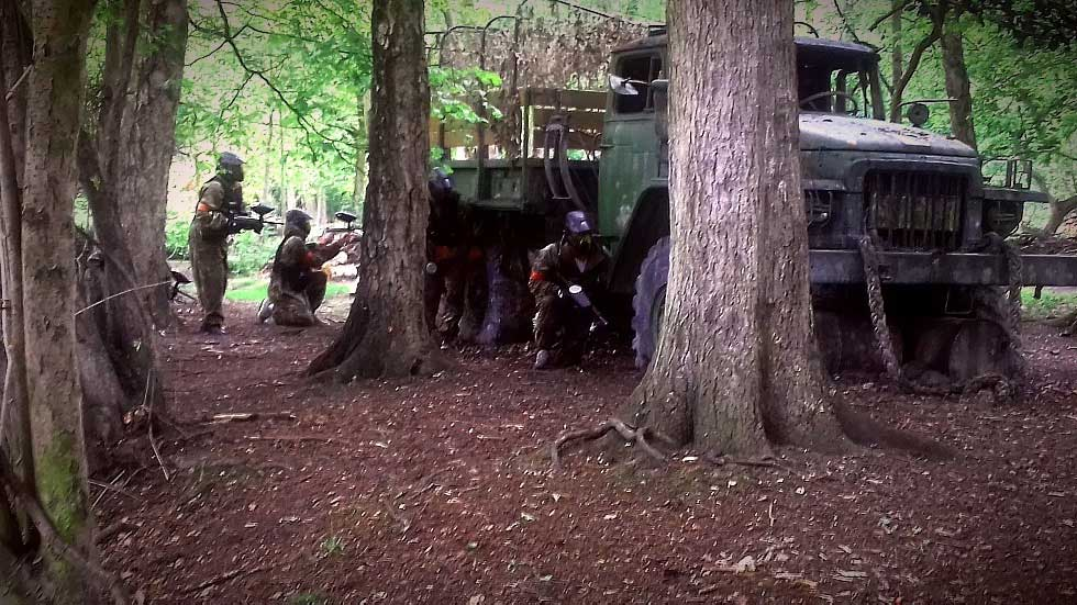 paintballers behind military truck for cover