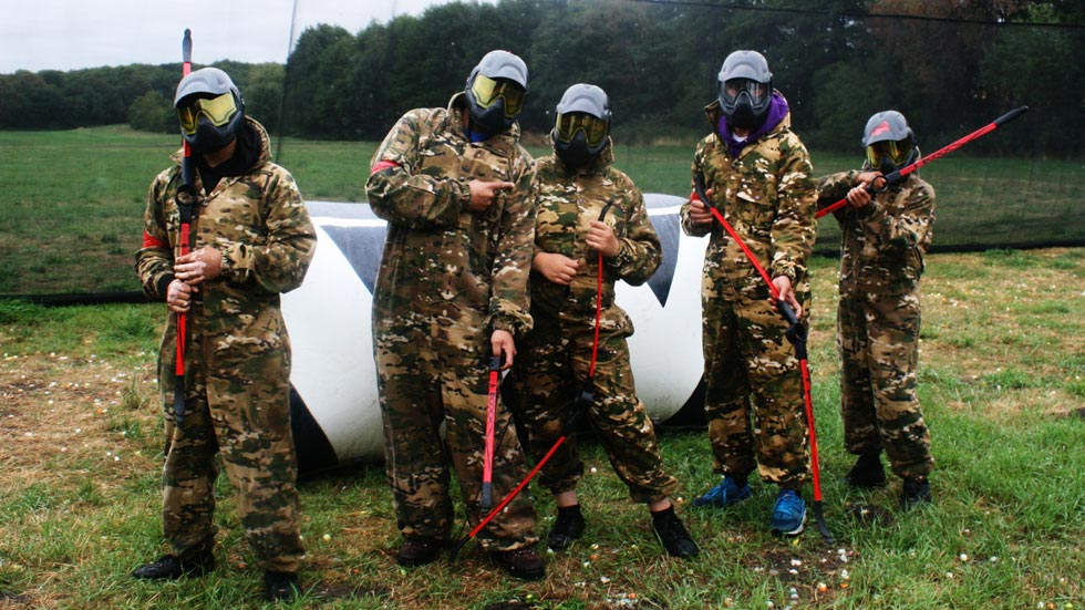 group of players in protective goggles and coveralls, with bows