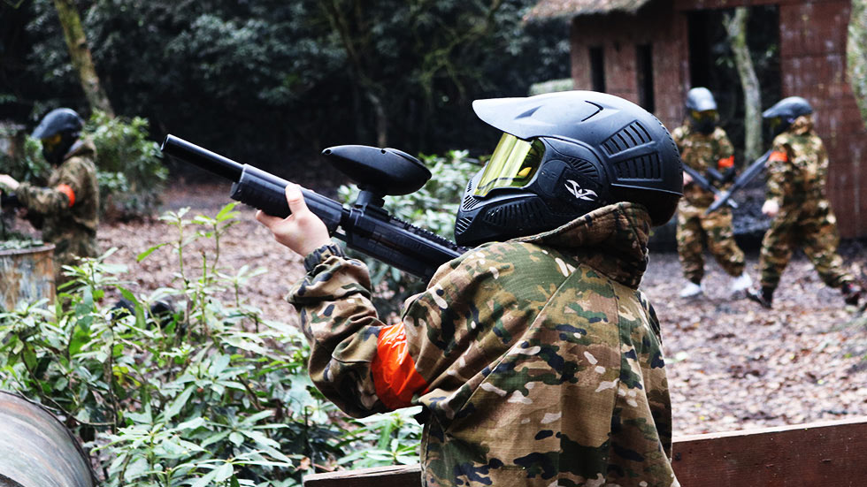 young player playing mini paintball with group in background