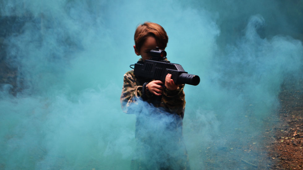 kid playing laser quest in smoke grenade cover