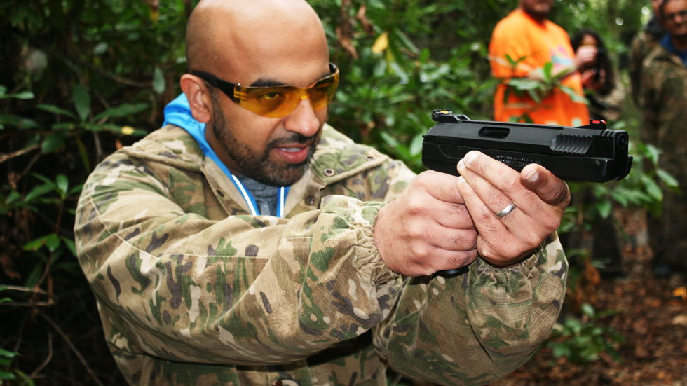 man with eye protection shoots air pistol